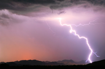 A bright lightning strike illuminating the Buckeye Foothills in Arlington during the 2012 Monsoon season, Arizona, United States of America, North America