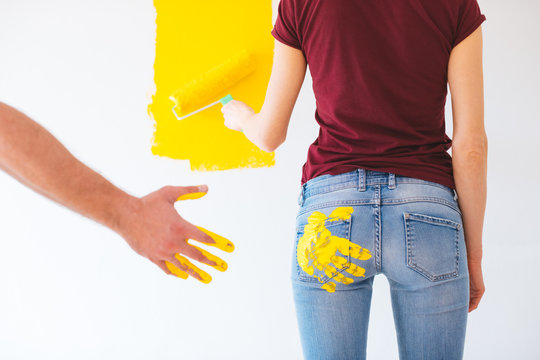 Rear view of woman painting the wall while man's hand leaves a mark on her buttock with yellow paint - gender discrimination, sexual abuse at work, harassment, violence, rape, metoo concept