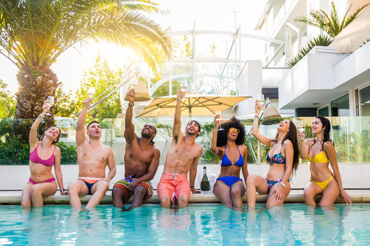 Front view of group of friends at swimming pool party celebrating with white-wine champagne and swim wear.