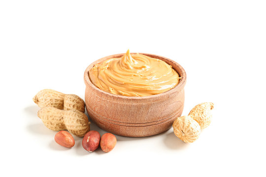 Creamy peanut butter in glass bowl and peanut isolated on white background. A traditional product of American cuisine
