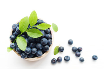 Fresh bilberry in a wooden bowl on a white background, top view