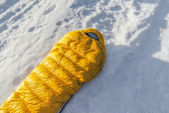 Yellow down sleeping bag lying on the snow. Warm sleeping sack on the ground on snow covered ground. Outdoor equipment.