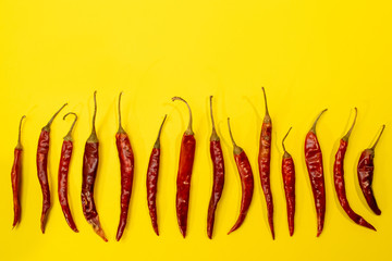 Red Chile de árbol chilis layed out in row on fun vibrant yellow background