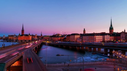 Wall Mural - Stockholm, Sweden. Time-lapse of Gamla Stan in Stockholm, Sweden with landmarks like Riddarholm Church during the sunrise. View of old buildings and car traffic at the bridge