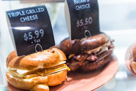Triple grilled cheese bagel sandwich sign with prices on display with bread, meat in store, shop, fast food on plate