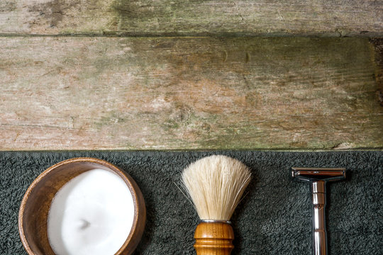 Retro safety razor, shaving brush and lather in bowl. Old-school wet shaving in rustic wooden table, with copy space.