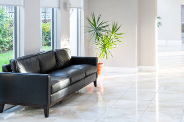 Black leather couch, sofa with green potted palm tree plant in pot with tiles, tiled floor in hall, room, lobby of residential, condo, condominium house, building, complex with bright, natural light Wall mural