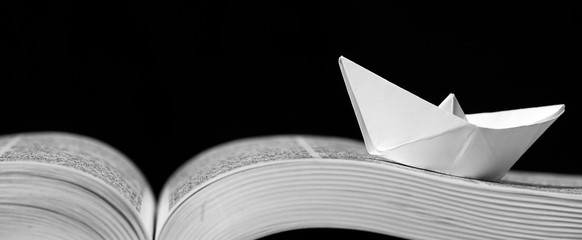 Paper boat on the opened book