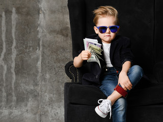 Portrait of self-confident rich kid boy siting in luxury armchair with bundles of dollars cash in...