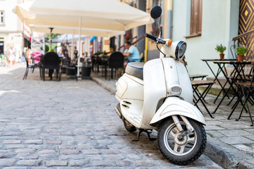 Closeup of white scooter parked by European cafe with bokeh background of outdoor restaurant in summer in Lviv or Lvov, Ukraine city