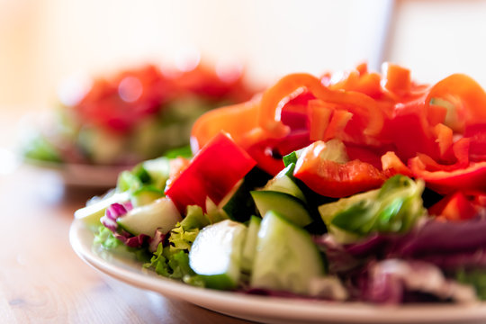 Healthy vegan vegetarian lunch or dinner green vegetables red bell pepper salad with nobody and two plates in bokeh background