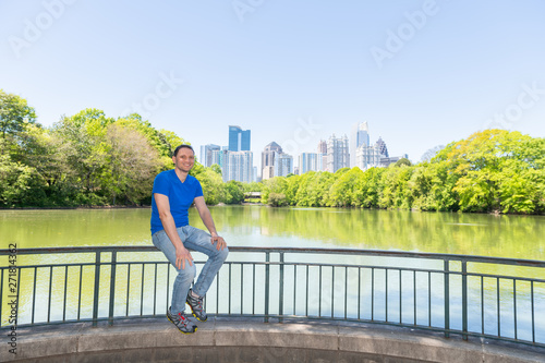 Young happy man sitting on railing in Piedmont Park in