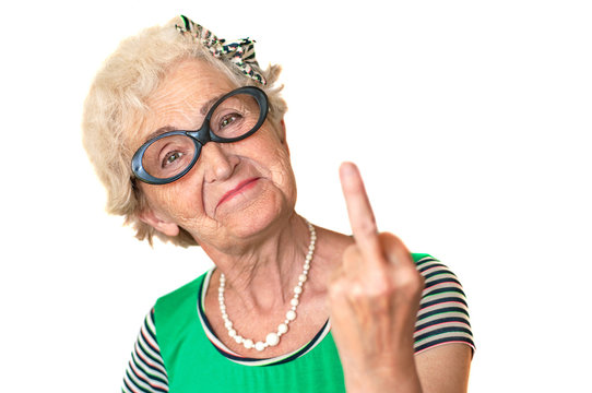 An older woman with an angry facial expression shows fuck you. Isolated The concept of discontent and protest of old men