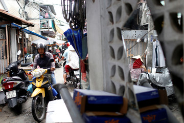 A motorbike is driven in an alley at Ma Lang slum in Ho Chi Minh city