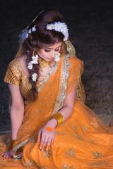 sitting woman wearing orange sari dress