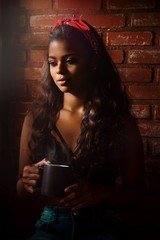 woman standing in front of brick wall while holding black ceramic mug