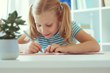 Portrait of schoolgirl at classroom writing at the table