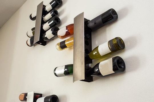 wine bottles in modern rack on white wall in the living room