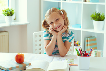 Portrait of cute school girl sitting at the white table at light classroom