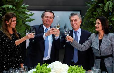 Argentina's President Mauricio Macri, first lady Juliana Awada, Brazil's President Jair Bolsonaro and his wife, Michelle Bolsonaro toast at the Casa Rosada government house in Buenos Aires