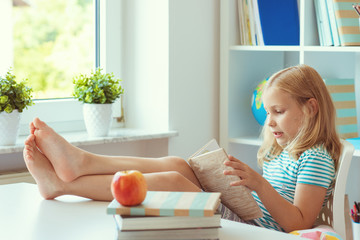 Portrait of funny little school girl relaxing reads book at the table in room at home