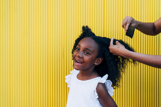 Mother doing daughter's afro hair