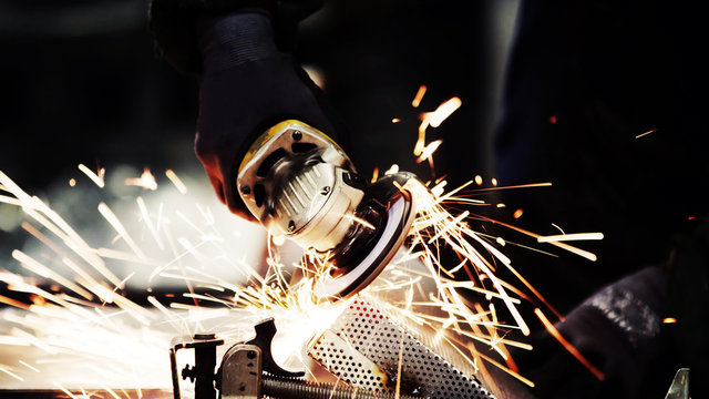 close up of a grinder machine cutting steel with metal sparks and dark black copy space background.