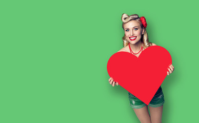 Photo of happy pin up girl holding red paper heart shape, over green color background. Copy space.