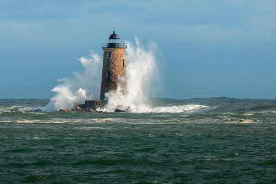 Huge Waves Surround Whaleback Lighthouse as Sun breaks Through Clouds in Maine in New England