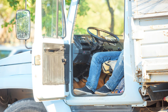 A man sitting behind the wheel of a truck. A man in blue jeans. The transmission panel and steering wheel in the truck.