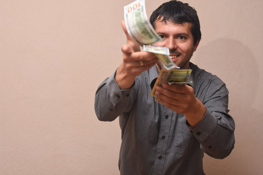 Concept of success, Young businessman throwing money. Man throwing hundred dollar bills in the air