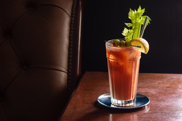 Spicy Bloody Mary Cocktail with Garnish of Celery, Lemon, and Olives in Glass in Dark Luxurious Bar