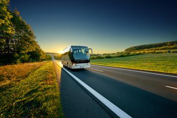 Fotobehang - White bus traveling on the asphalt road around line of trees in rural landscape at sunset