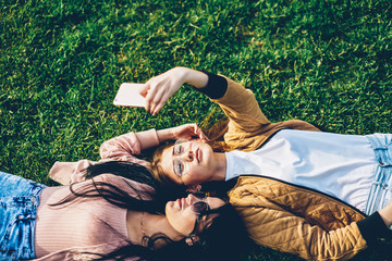 Two students in sunglasses lying on grass in park and making selfies photos on digital telephone device enjoying free time together in park.Female bloggers taking pictures for publication on webpage
