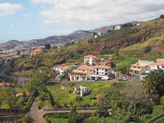 an aerial view of funchal in madeira with houses and farms on a mountainside with the city and coast in the distance