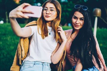 Attractive young women with stylish sunglasses making selfie photos on smartphone spending free time together in park.Friends taking pictures on digital mobile phone for publishing in own blog