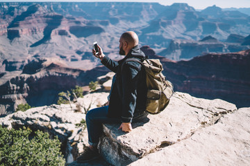 Male traveler with backpack using smartphone camera for taking picture of beautiful landscape of Grand Canyon National Park, hipster guy wanderlust checking good mobile connection sitting on hill peak