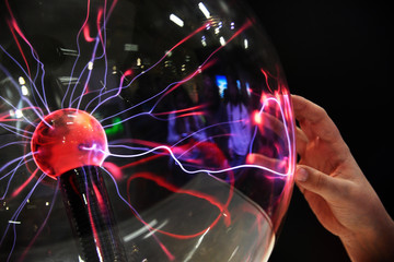 Hand touching with finger electric plasma in glass sphere.