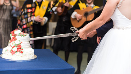 Close-up hands of bride and groom cutting wedding cake with a sword.