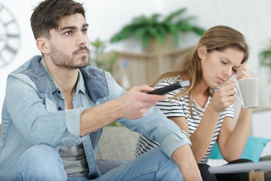 upset woman looking at tired man on sofa watching tv