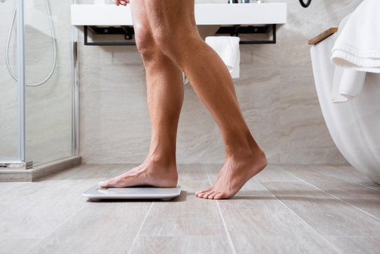 Man standing on the toes while putting foot on the scales