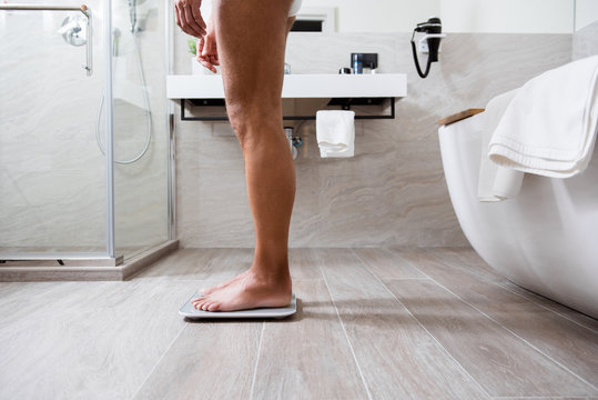 Side view of the barefooted person weighing on the floor scales