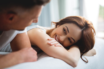 Cute woman smiling to man while lying next to him