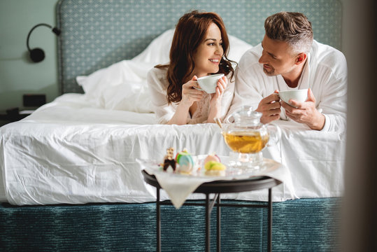 Lovely couple lying on the bed and drinking tea
