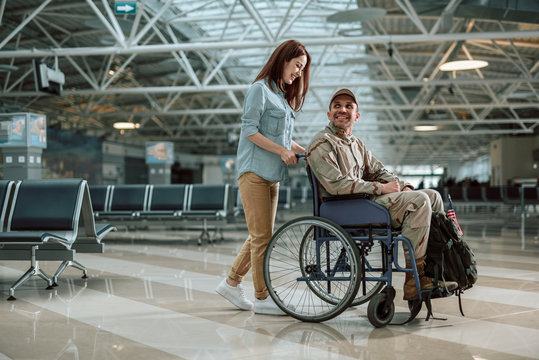 Beautiful wife carrying wheelchair and situating behind her husband in military uniform
