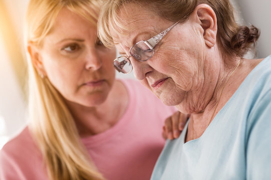 Young Adult Woman Consoles Sad Senior Adult Female