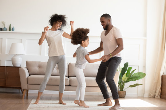 Happy funny active african family with daughter dancing at home