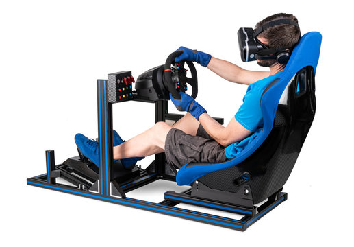 gamer in blue tshirt with VR virtual reality glasses training on simracing aluminum simulator rig for video game racing. Motorsport car bucket seat steering wheel pedals isolated white background