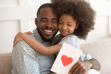 African dad embracing daughter holding greeting card on fathers day