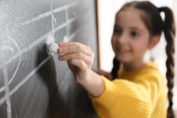 Little girl writing music notes on blackboard in classroom, closeup